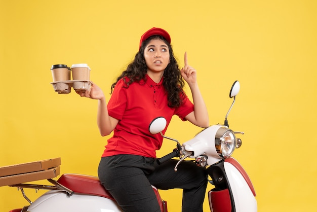 Front view female courier on bike holding coffee cups on yellow background worker service uniform woman delivery work
