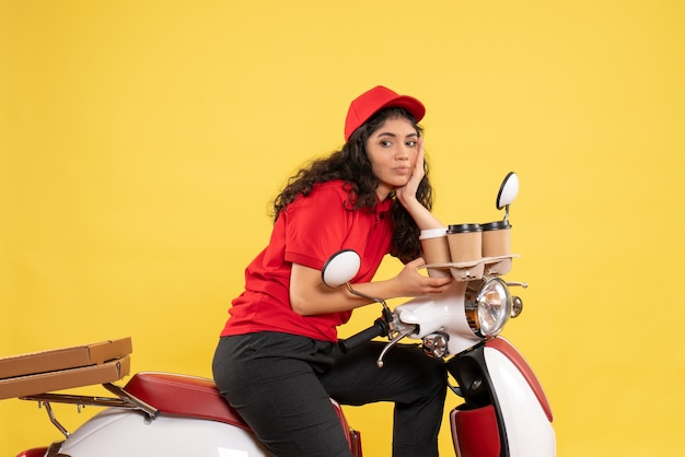 Front view female courier on bike holding coffee cups on yellow background worker uniform job woman delivery work