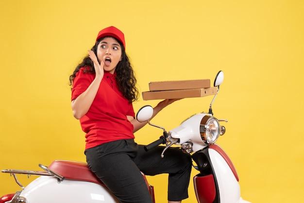 Corriere femminile vista frontale in bicicletta che tiene scatole per pizza su sfondo giallo lavoro lavoratore donna consegna lavoro