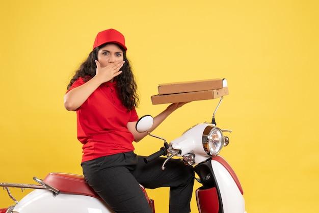 Corriere femminile vista frontale in bicicletta che tiene scatole per pizza su sfondo giallo lavoratore servizio uniforme lavoro donna consegna lavoro