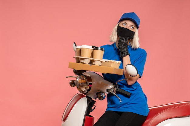 Front view female courier on bike with coffee cups on a pink