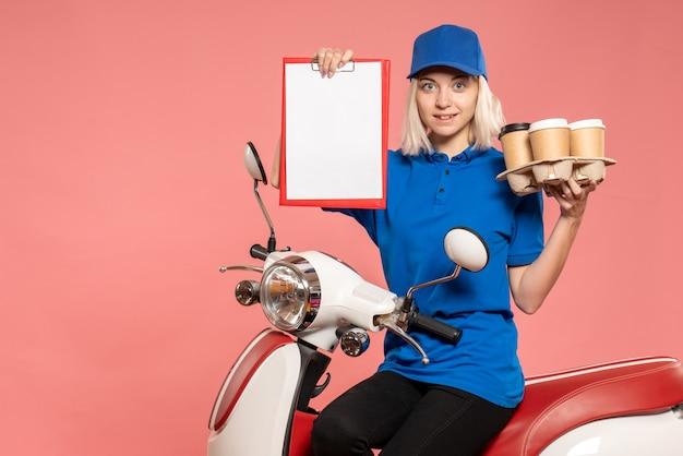 Corriere femminile di vista frontale sulla bici con le tazze di caffè sulla rosa