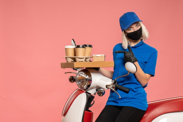 Front view female courier on bike with coffee cups on pink