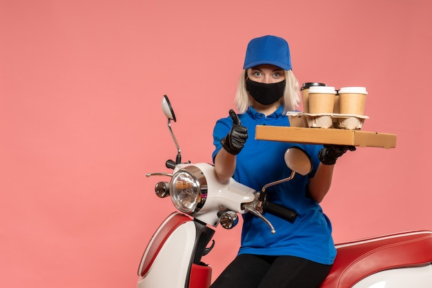 Front view female courier on bike with coffee cups on the pink
