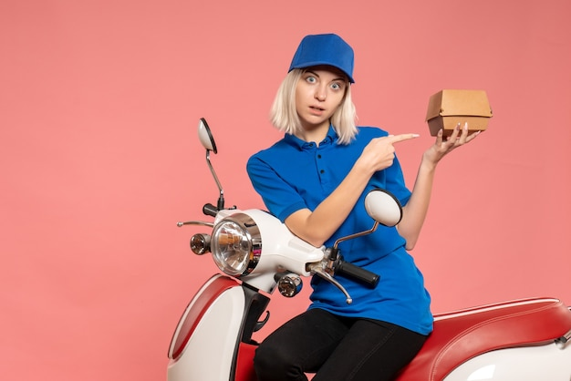 Front view female courier on bike with little food package on pink