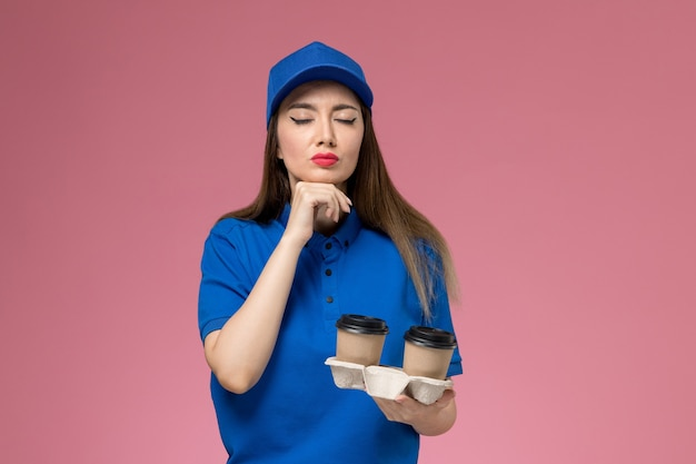 Front view female courier in blue uniform and cape holding brown delivery coffee cups on the pink wall