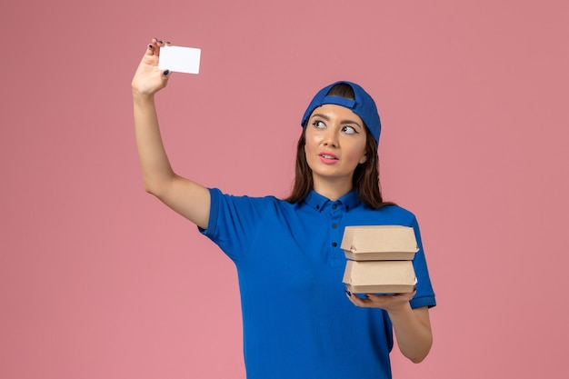 Front view female courier in blue uniform cape holding card and little delivery packages on light pink wall, service employee delivery work