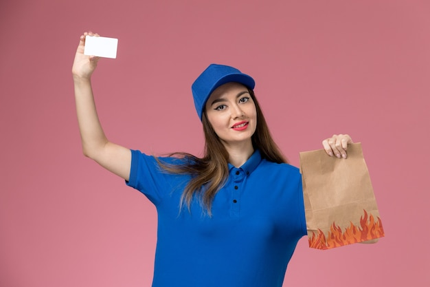 Front view female courier in blue uniform and cape holding card and paper food package on the pink desk