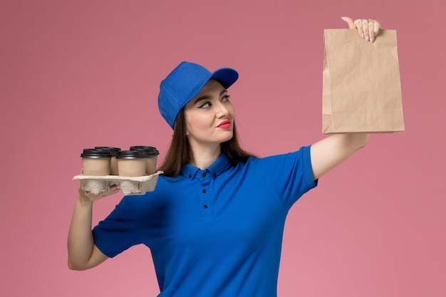 Front view female courier in blue uniform and cape holding coffee cups and food package on the pink desk