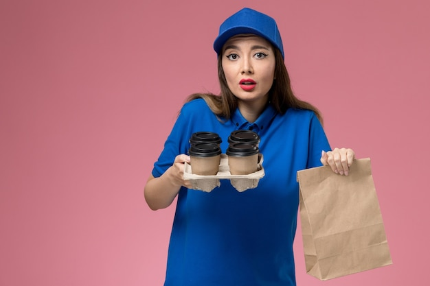 Front view female courier in blue uniform and cape holding coffee cups and food package on pink wall