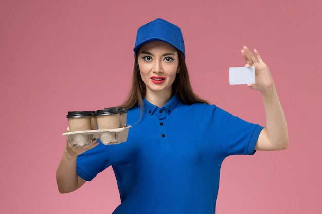 Front view female courier in blue uniform and cape holding coffee cups and white card on pink wall