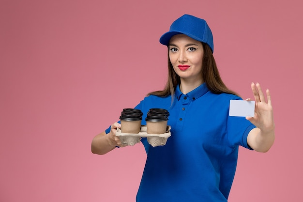 Front view female courier in blue uniform and cape holding coffee cups white card on pink wall
