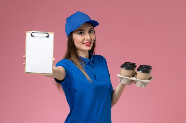 Front view female courier in blue uniform and cape holding coffee cups with notepad on pink wall  woman