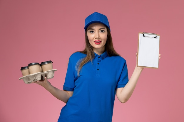 Front view female courier in blue uniform and cape holding coffee cups with notepad on pink wall  work female woman