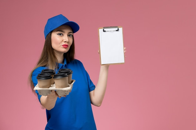 Front view female courier in blue uniform and cape holding coffee cups with notepad on pink wall  work woman