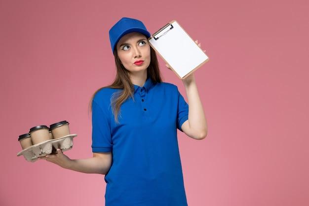 Corriere femminile di vista frontale in uniforme blu e mantello che tiene le tazze di caffè con il blocco note che pensa sul muratore rosa