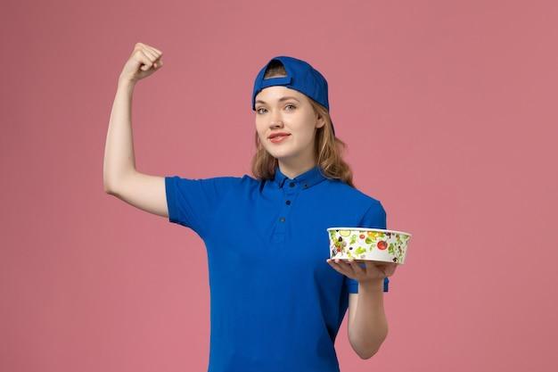 Corriere femminile di vista frontale nella ciotola di consegna della tenuta del capo uniforme blu che flette sulla parete rosa-chiaro, impiegato di consegna di servizio