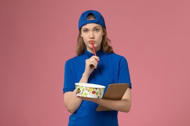 Front view female courier in blue uniform cape holding delivery bowl and notepad writing on the light pink desk service delivery employee