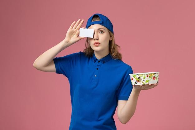 Corriere femminile di vista frontale in mantello blu uniforme che tiene la ciotola di consegna con la carta sulla parete rosa chiaro, impiegato di consegna di servizio