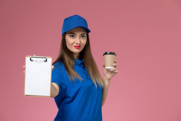 Front view female courier in blue uniform and cape holding delivery coffee cup and notepad on the light-pink desk