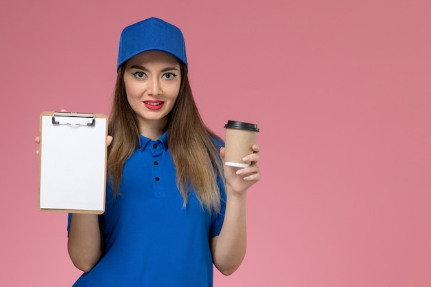 Front view female courier in blue uniform and cape holding delivery coffee cup and notepad smiling on pink wall  worker