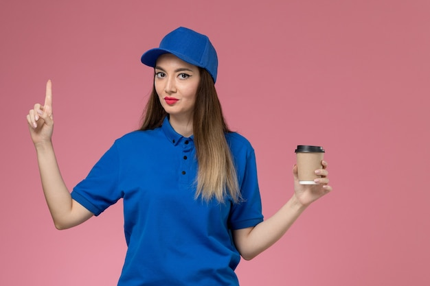 Front view female courier in blue uniform and cape holding delivery coffee cup on the pink wall girl woman