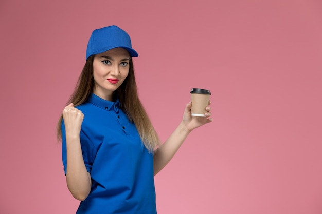 Front view female courier in blue uniform and cape holding delivery coffee cup on the pink wall job girl woman worker work