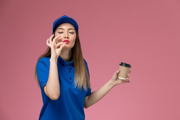Front view female courier in blue uniform and cape holding delivery coffee cup on the pink wall job girl woman worker