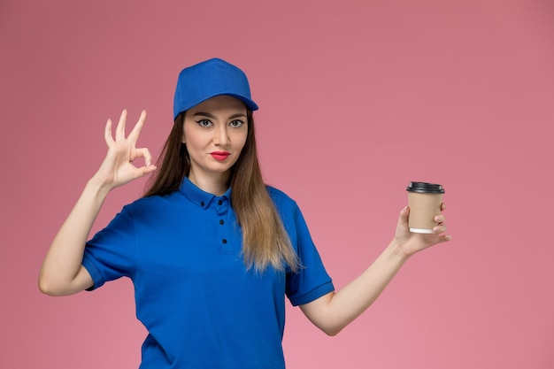 Front view female courier in blue uniform and cape holding delivery coffee cup on the pink wall job girl woman