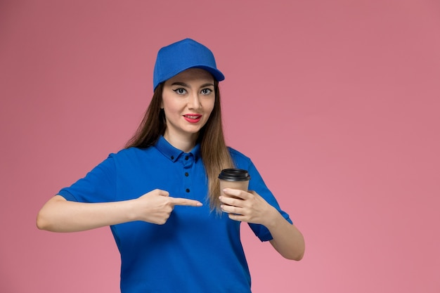 Front view female courier in blue uniform and cape holding delivery coffee cup on the pink wall job worker woman