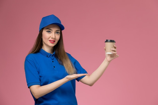 Front view female courier in blue uniform and cape holding delivery coffee cup on the pink wall job worker work