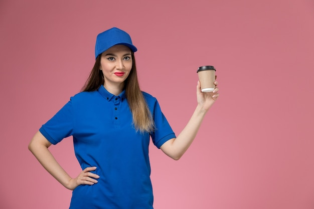 Front view female courier in blue uniform and cape holding delivery coffee cup posing on the pink wall job