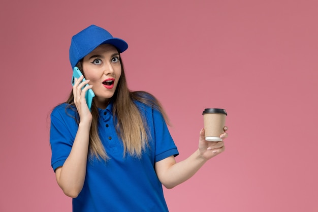 Front view female courier in blue uniform and cape holding delivery coffee cup and using phone on the pink wall