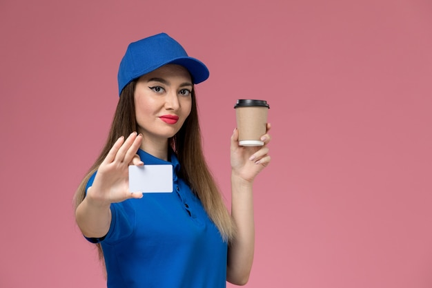 Front view female courier in blue uniform and cape holding delivery coffee cup and white card on pink wall