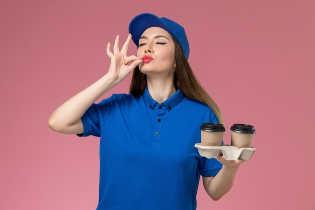 Front view female courier in blue uniform and cape holding delivery coffee cups on pink desk worker