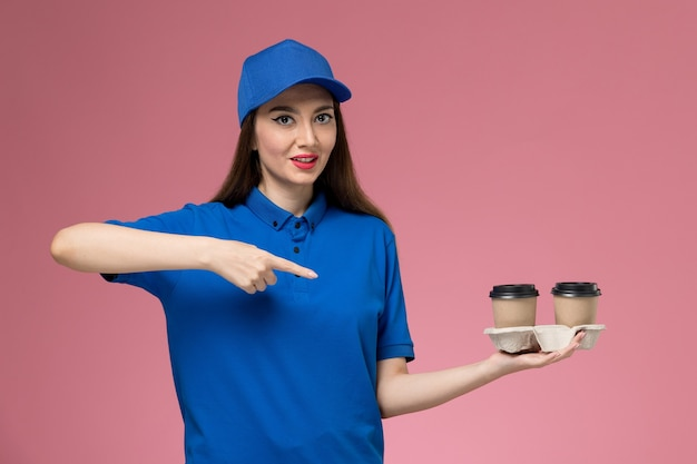 Front view female courier in blue uniform and cape holding delivery coffee cups on the pink wall job