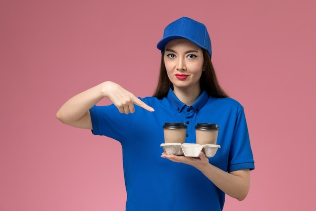 Front view female courier in blue uniform and cape holding delivery coffee cups on pink wall