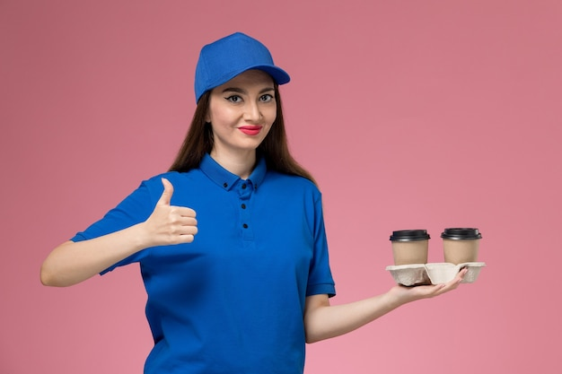 Front view female courier in blue uniform and cape holding delivery coffee cups smiling on pink desk