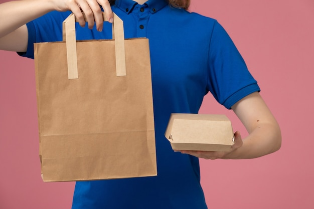 Front view female courier in blue uniform cape holding delivery packages on the pink wall, employee service delivery