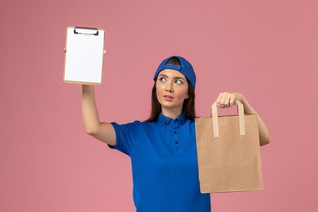 Corriere femminile di vista frontale in capo uniforme blu che tiene il pacchetto di carta di consegna e blocco note sulla parete rosa, consegna degli impiegati di servizio di lavoro