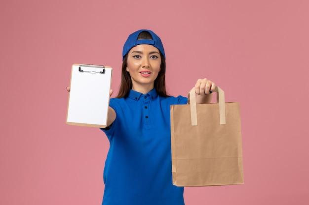 Corriere femminile di vista frontale in mantello uniforme blu che tiene il pacchetto di carta di consegna e blocco note sulla parete rosa, lavoratore di servizio che consegna