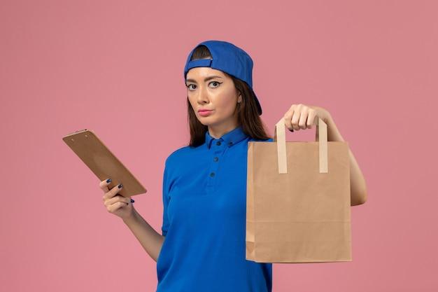 Corriere femminile di vista frontale in mantello uniforme blu che tiene il pacchetto di carta di consegna e blocco note sulla parete rosa, consegna degli impiegati di servizio