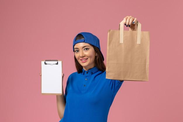 Corriere femminile di vista frontale in mantello uniforme blu che tiene il pacchetto di carta di consegna e blocco note sulla parete rosa, consegna degli impiegati del lavoro di servizio