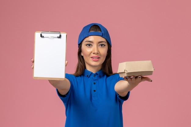 Corriere femminile di vista frontale in capo uniforme blu che tiene piccolo pacchetto di consegna vuoto con il blocco note sulla parete rosa-chiaro, consegna dell'azienda di servizio del dipendente