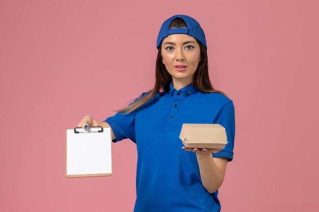 Corriere femminile di vista frontale in capo uniforme blu che tiene piccolo pacchetto di consegna vuoto con il blocco note sulla parete rosa chiaro, consegna del servizio di lavoro dei dipendenti