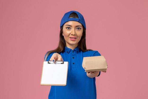 Corriere femminile di vista frontale in capo uniforme blu che tiene piccolo pacchetto di consegna vuoto con il blocco note sulla parete rosa chiaro, consegna di servizio dei dipendenti di lavoro