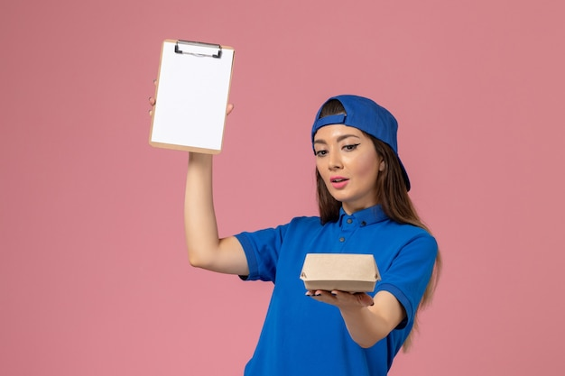 Corriere femminile di vista frontale in capo uniforme blu che tiene piccolo pacchetto di consegna vuoto con il blocco note sulla parete rosa, lavoro della ragazza di consegna dell'azienda di servizio degli impiegati