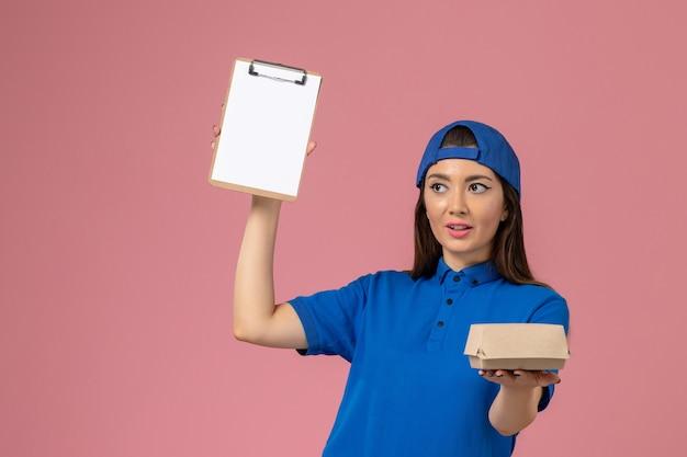 Corriere femminile di vista frontale in capo uniforme blu che tiene piccolo pacchetto di consegna vuoto con il blocco note sulla parete rosa, lavoro di lavoro di consegna dell'azienda di servizio degli impiegati