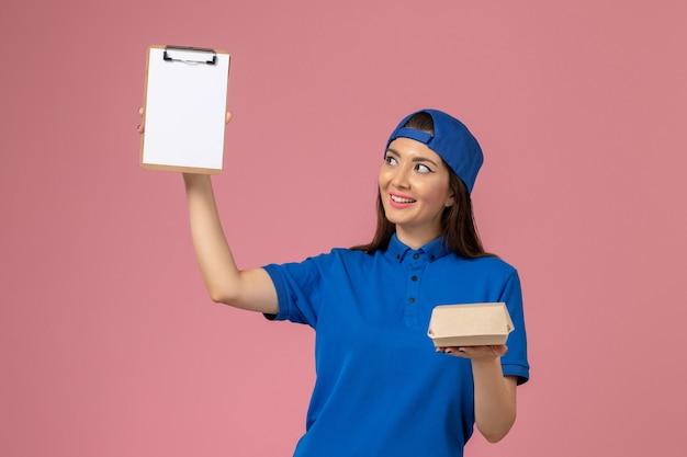 Corriere femminile di vista frontale in capo uniforme blu che tiene piccolo pacchetto di consegna vuoto con il blocco note sulla parete rosa, lavoro di consegna dell'azienda di servizio dei dipendenti