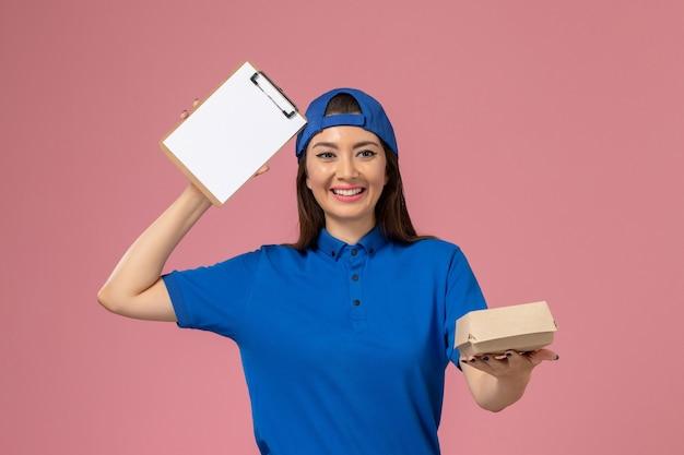 Corriere femminile di vista frontale in capo uniforme blu che tiene piccolo pacchetto di consegna vuoto con il blocco note sulla parete rosa, lavoratore di consegna dell'azienda di servizi del dipendente